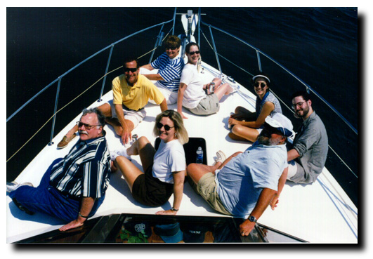 The Morning Crew on the Yacht Lyle Dean. (Clockwise from bottom left) News anchor Dick Sutliff, sports director Dave Eanet, assisstant Diane Huske, producer Audrey Clarke, traffic reporter Mary Van De Velde, assistant producer Scott Cameron, Bob, program director Mary June Rose