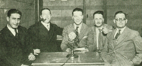 """A collection of 1920s celebrities gathered around a WGN microphone for a chat: (L-R) All-American halfback Benny Friedman; Count Felix Luckner, """"The Sea Devil;"""" Chicago Tribune foreign correspondent Floyd Gibbons; Quin Ryan; and Frank Willard, of Moon Mullins."""