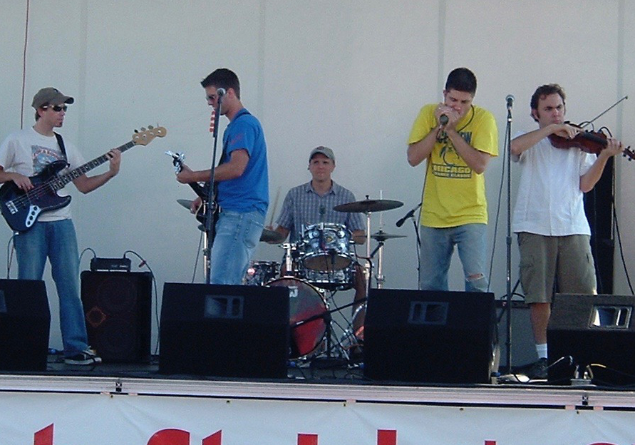 OTL host Mike Stephen (in the yellow shirt and on the harmonica) and his old band Detagoh were no stranger to the festival circuit. [photo circa 2005 at the St. John Summerfest in Indiana]