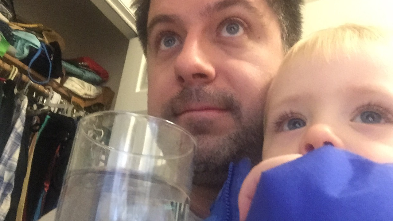 """OTL host Mike Stephen III and his son Mike Stephen IV watch an episode of Elmo's World while enjoying a tall glass of Chicago tap water. (Text """"LEAD"""" to 312-697-1791 to find out more about potential lead poisoning in your area.)"""