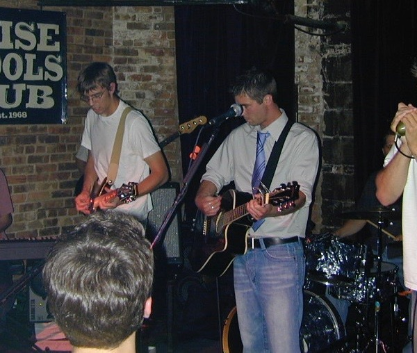 "OTL host Mike Stephen (far right, on harmonica) and his band Detagoh rock Wise Fools Pub in 2005. [not pictured: ""Socks"" the bass player]"
