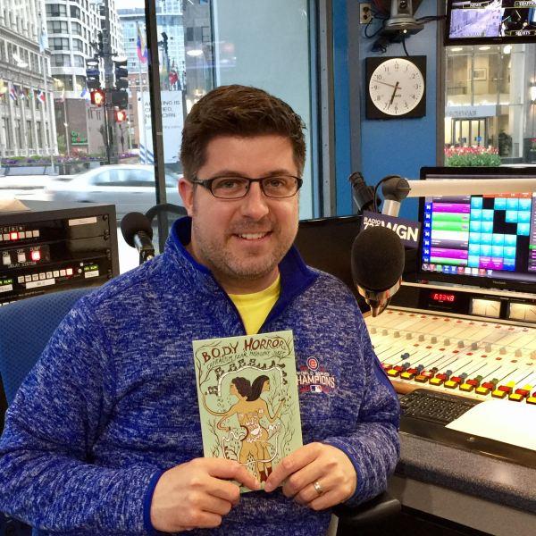 OTL host Mike Stephen holds a copy of Anne Elizabeth Moore's latest book Body Horror: Capitalism, Fear, Misogyny, Jokes.