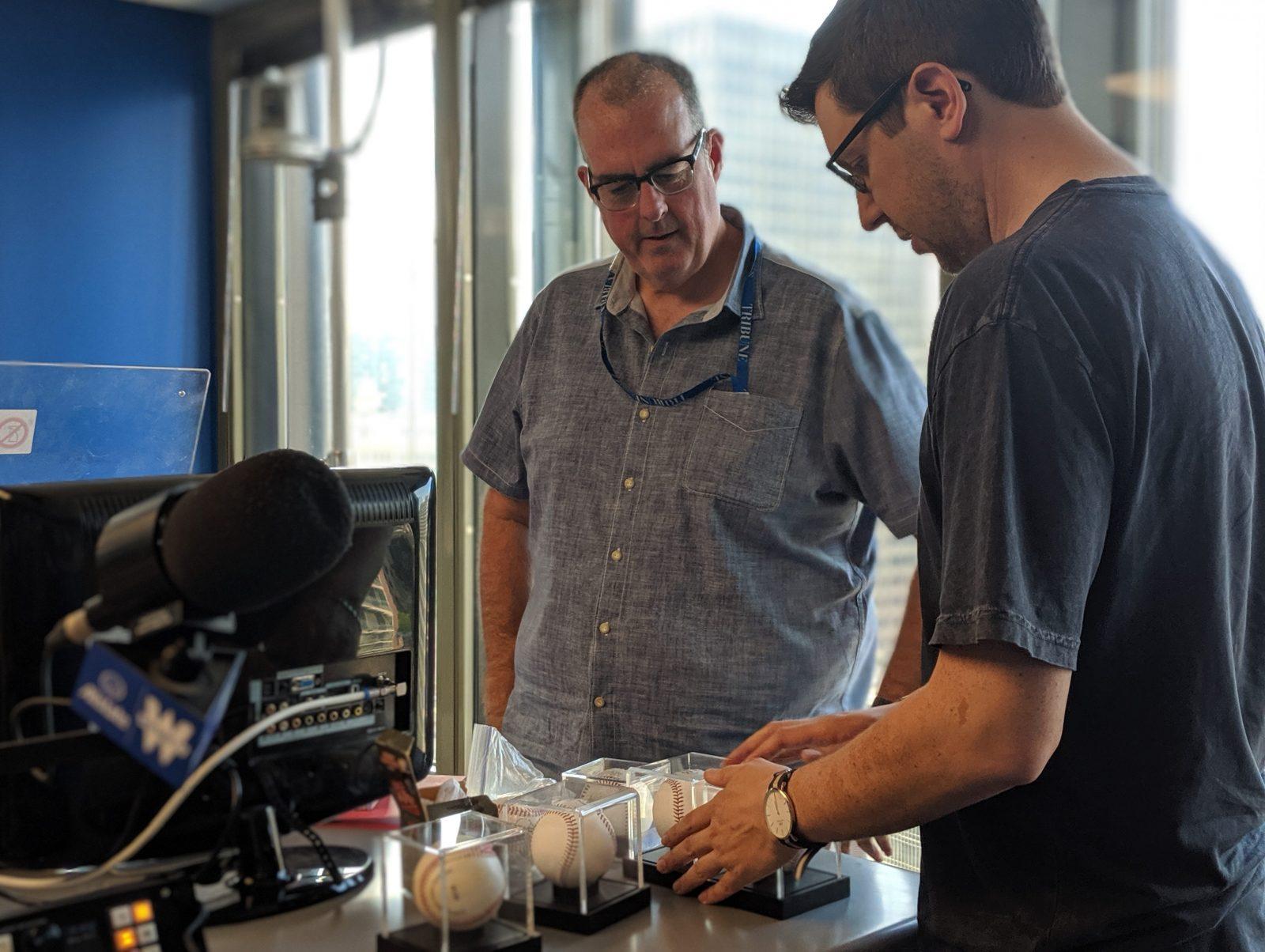 Appraiser Michael Osacky, right, examines sports memorabilia in-studio with Brian Noonan, left